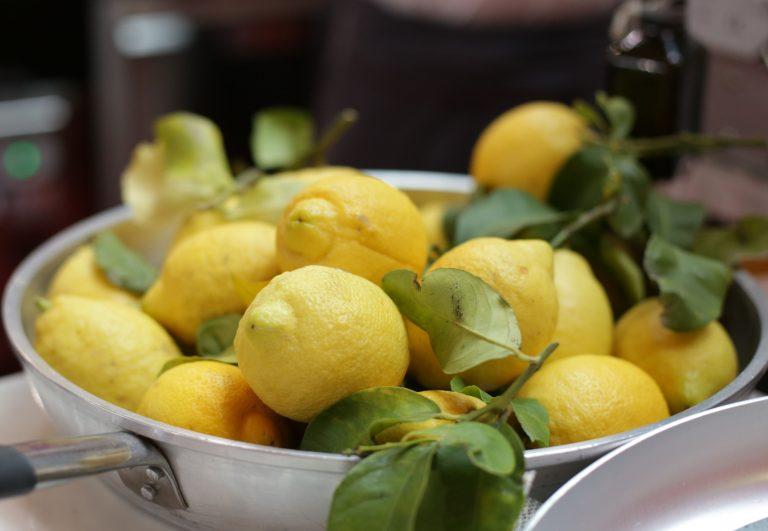 Bere acqua e limone al mattino fa bene o fa male? In foto, una pentola piena di limoni freschi