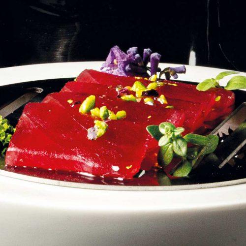 Tonno rosso crudo scaloppato con pistacchi, olio evo e sale Maldon su misticanza con spugna al basilico